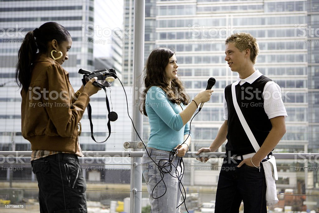 A young male teenager being interviewed by two young females royalty-free stock photo