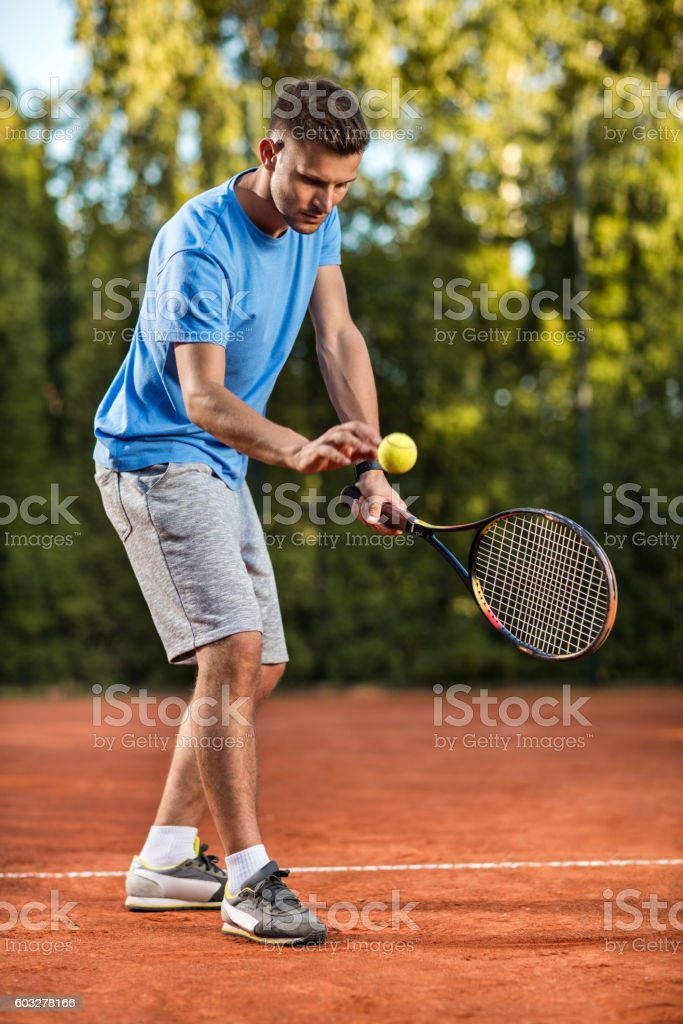 Young male tennis player preparing for serving on the court. stock photo