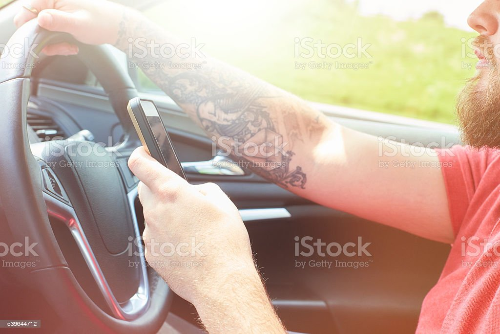 young male texting whilst driving stock photo