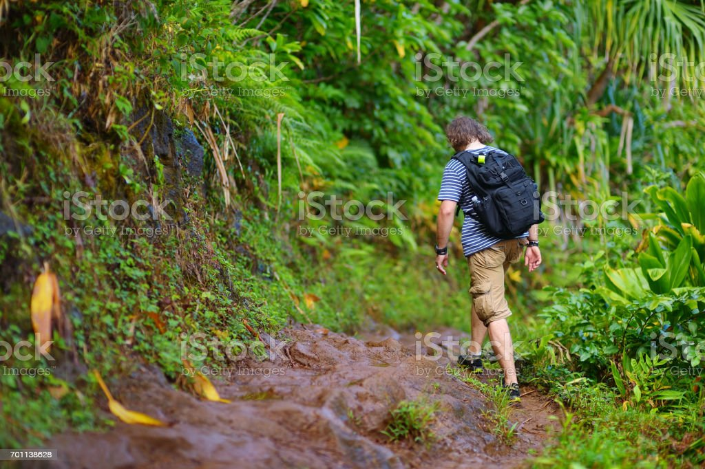 Young male tourist hiking on the famous Kalalau trail along Na Pali coast of the island of Kauai stock photo