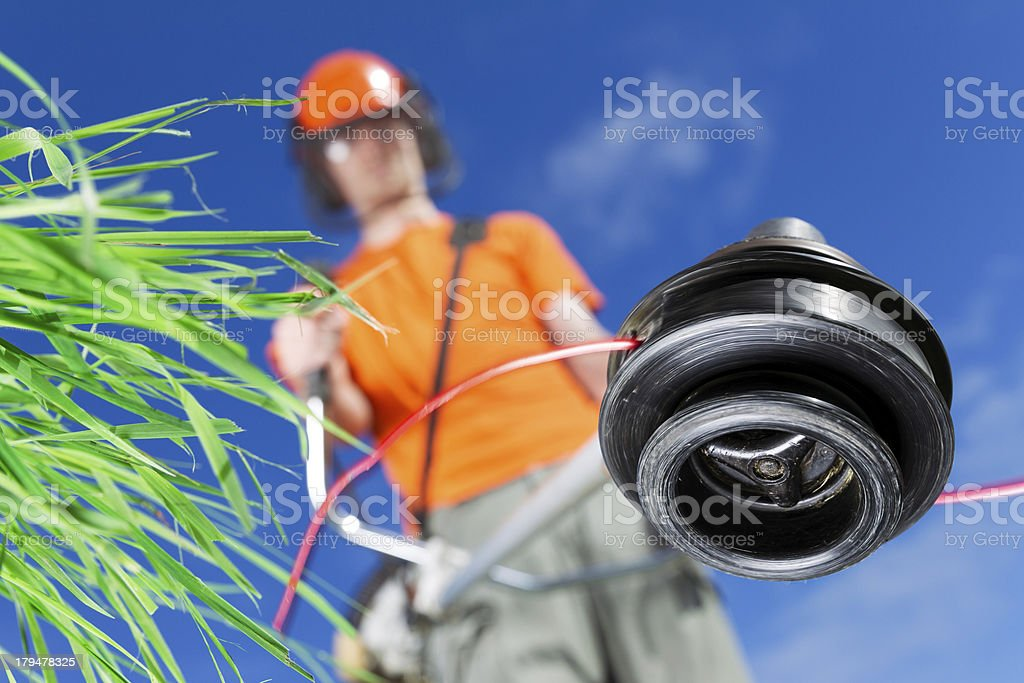 Young male using garden strimmer royalty-free stock photo