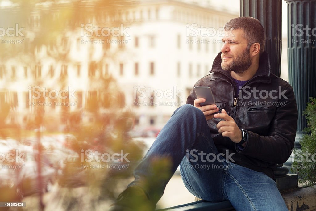 Young male using smartphone in the city stock photo
