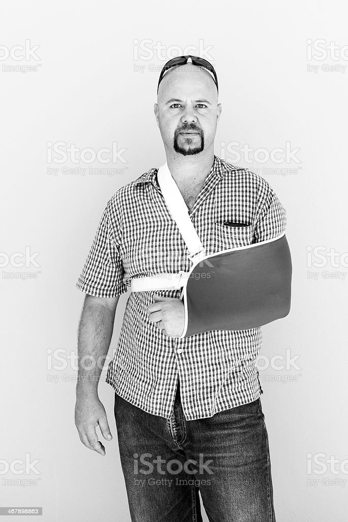 Young male with his broken arm in a sling stock photo