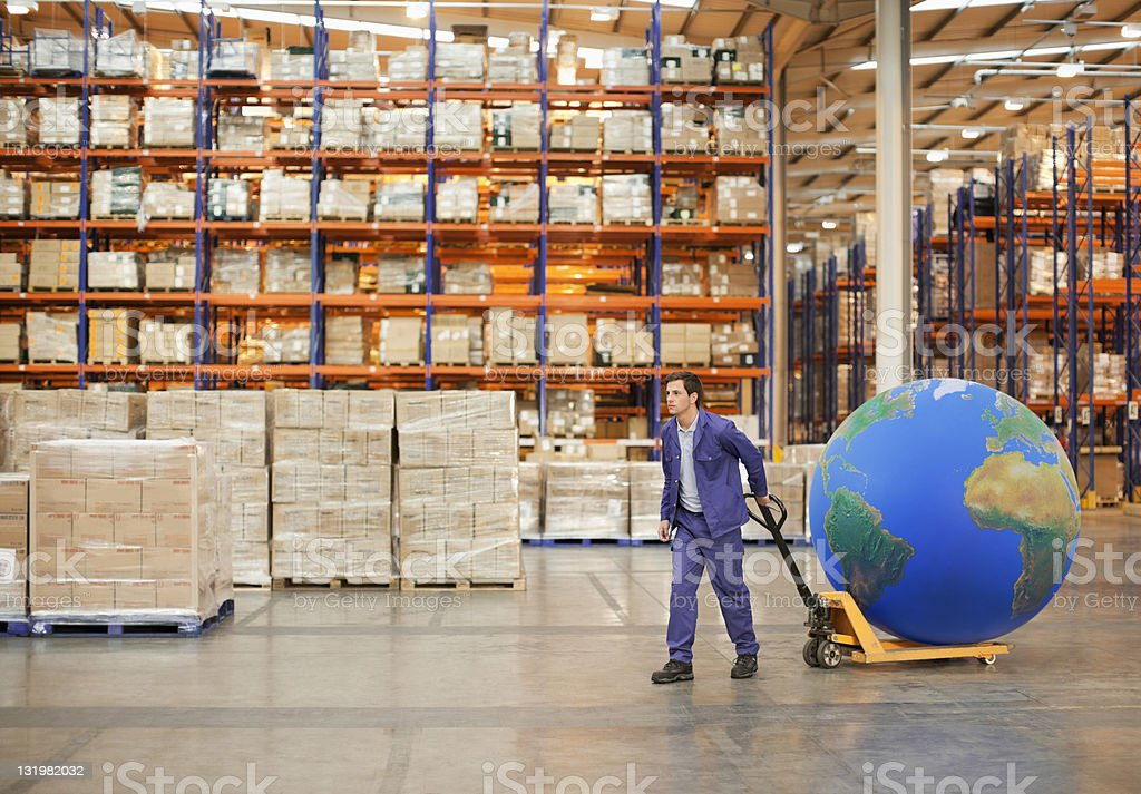 Young male worker pulling hand truck with large blue ball in warehouse stock photo