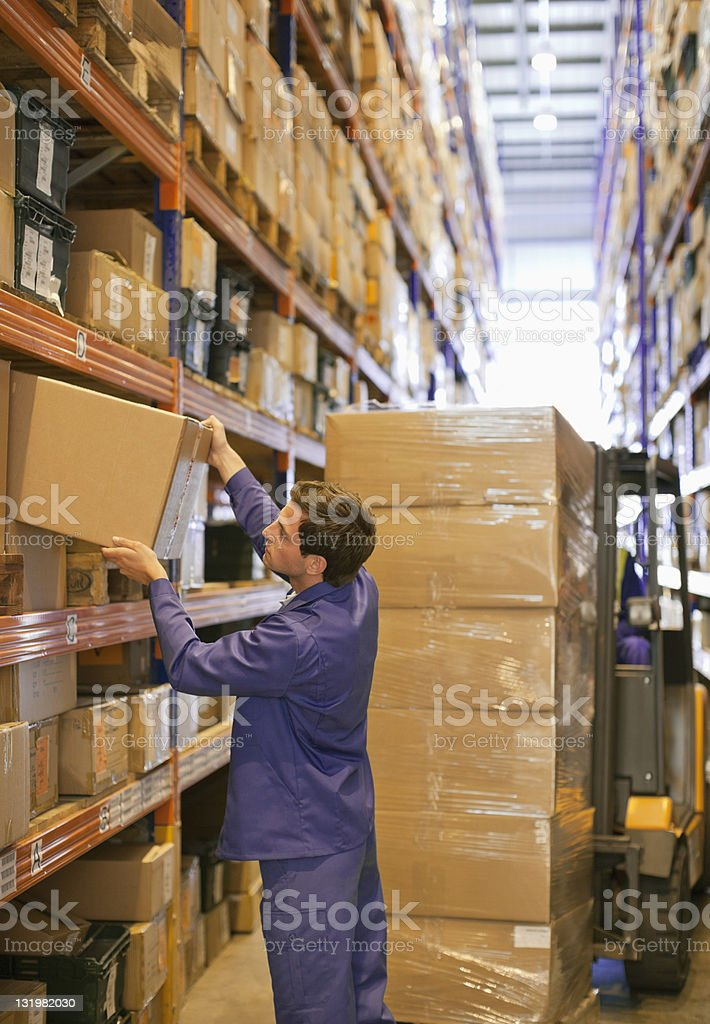 Young male worker pushing cardboard box in shelf royalty-free stock photo