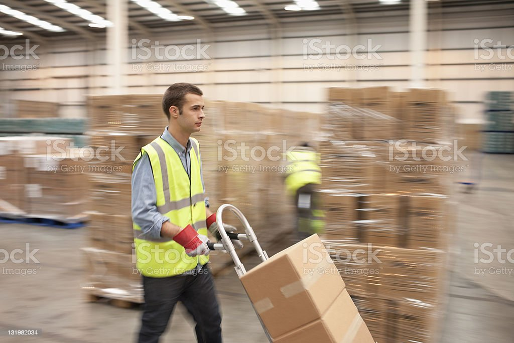 Young male worker pushing hand truck of cardboard boxes through warehouse stock photo