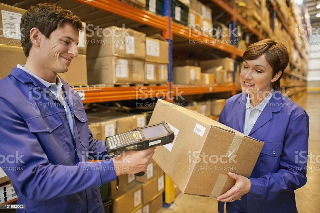 Young male worker scanning barcode while female holding the box stock photo