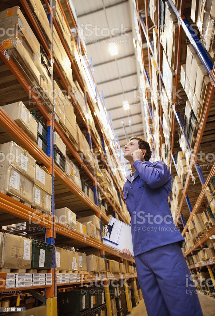 Young male worker talking on mobile phone while examining boxes in warehouse royalty-free stock photo