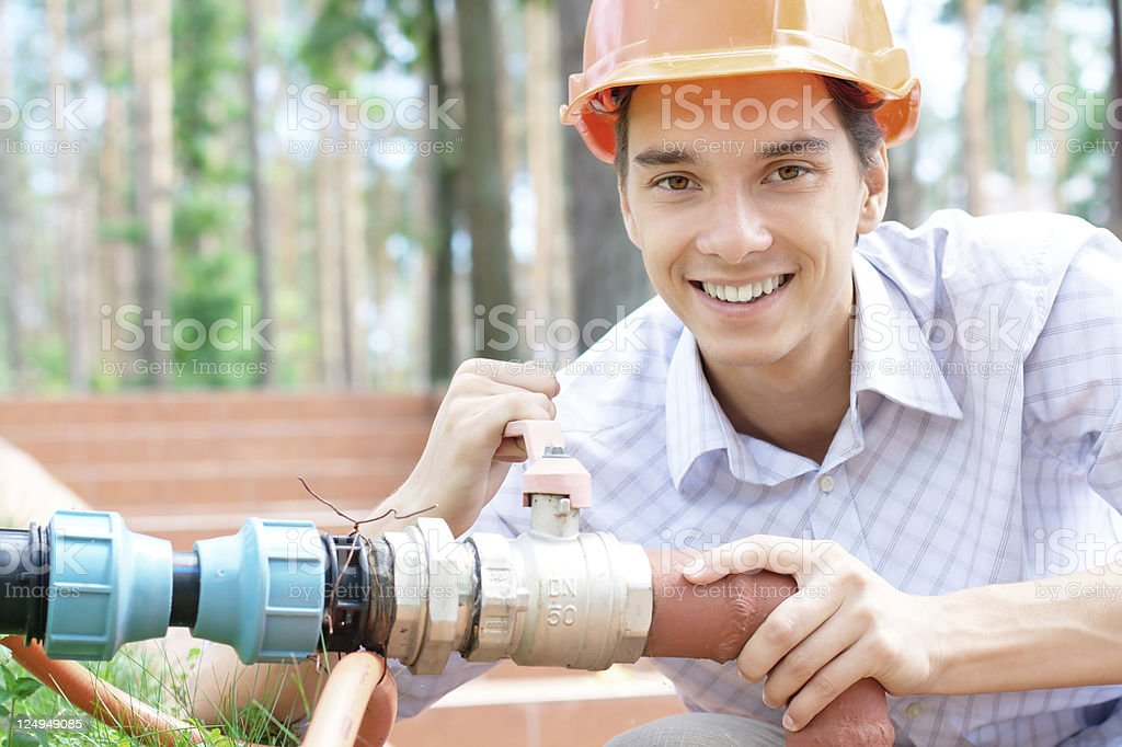 Young male worker working on a pipe royalty-free stock photo