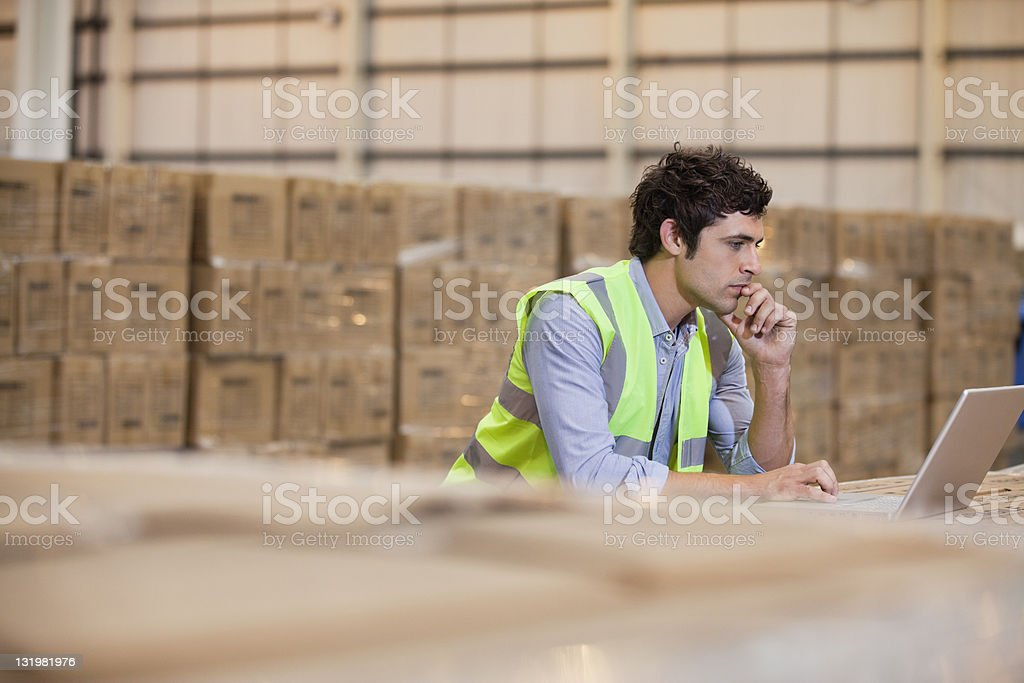Young male worker working on laptop in warehouse stock photo