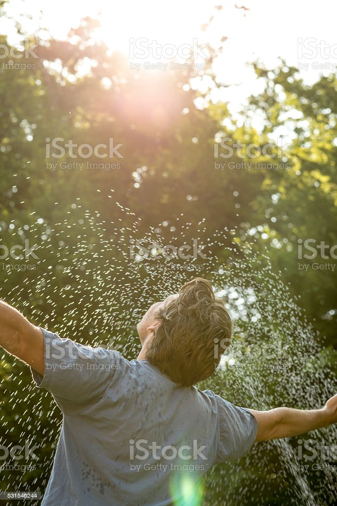 Young mam standing under a spray of water stock photo