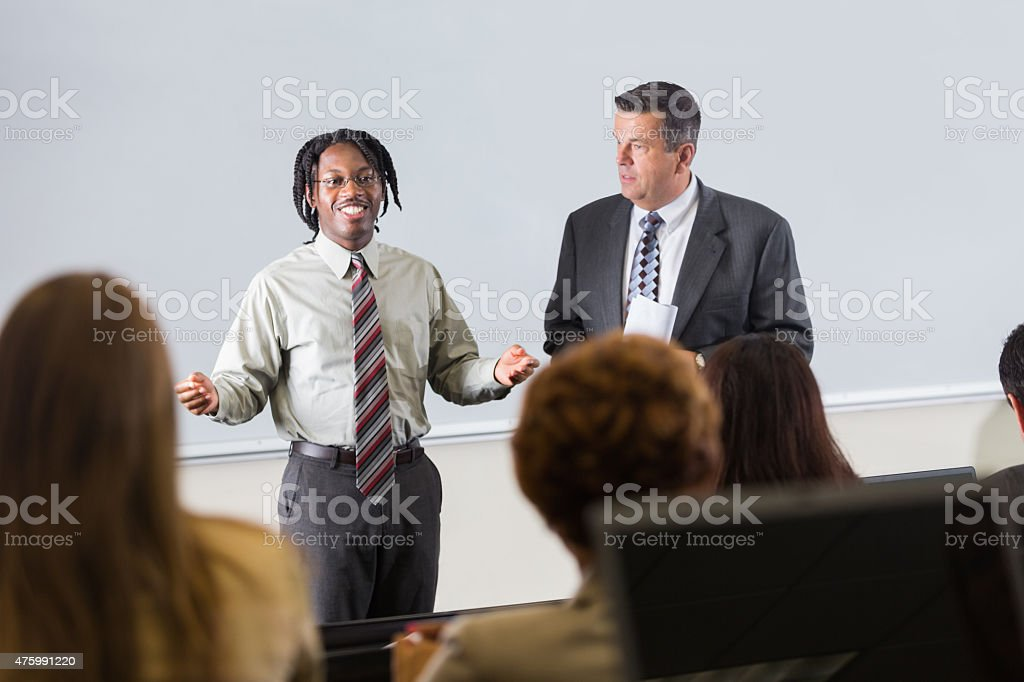 Young man addressing crowd during motivational speech or seminar event. stock photo