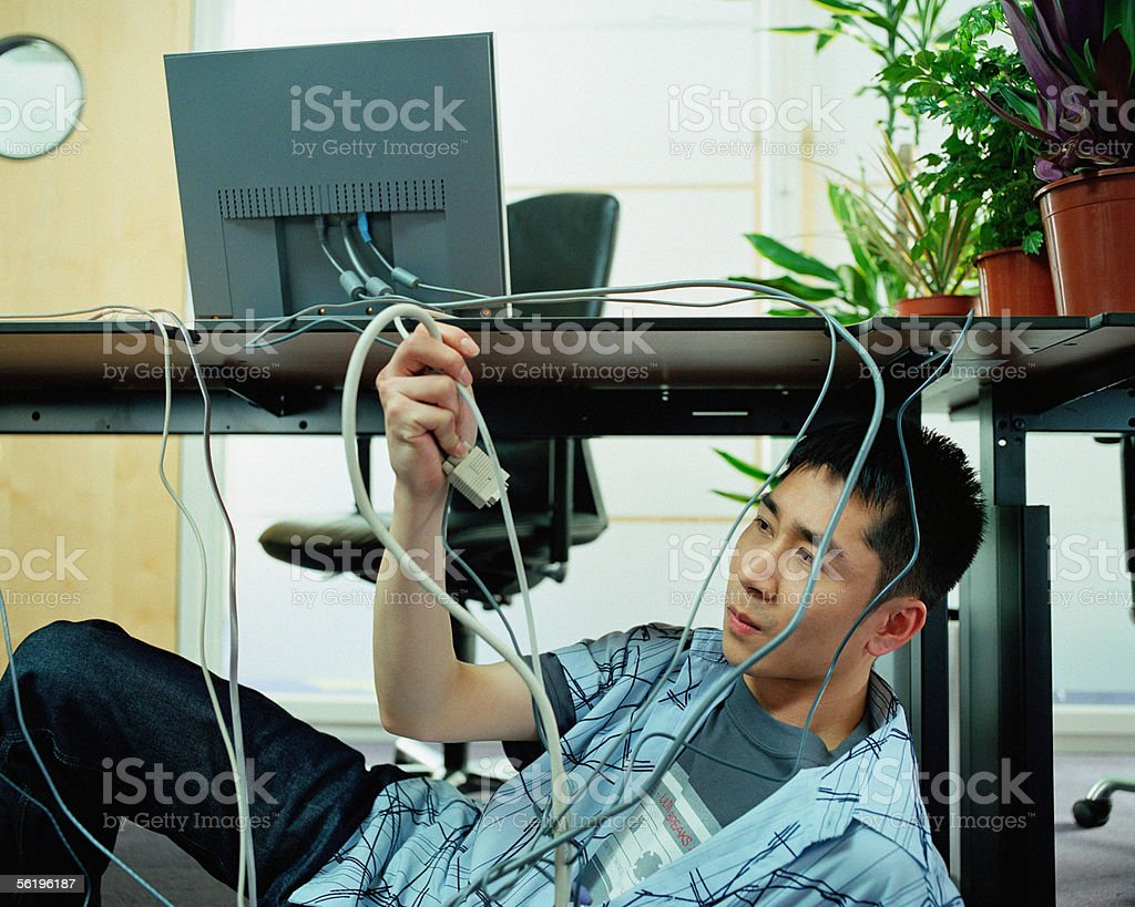 Young man adjusting computer cables royalty-free stock photo