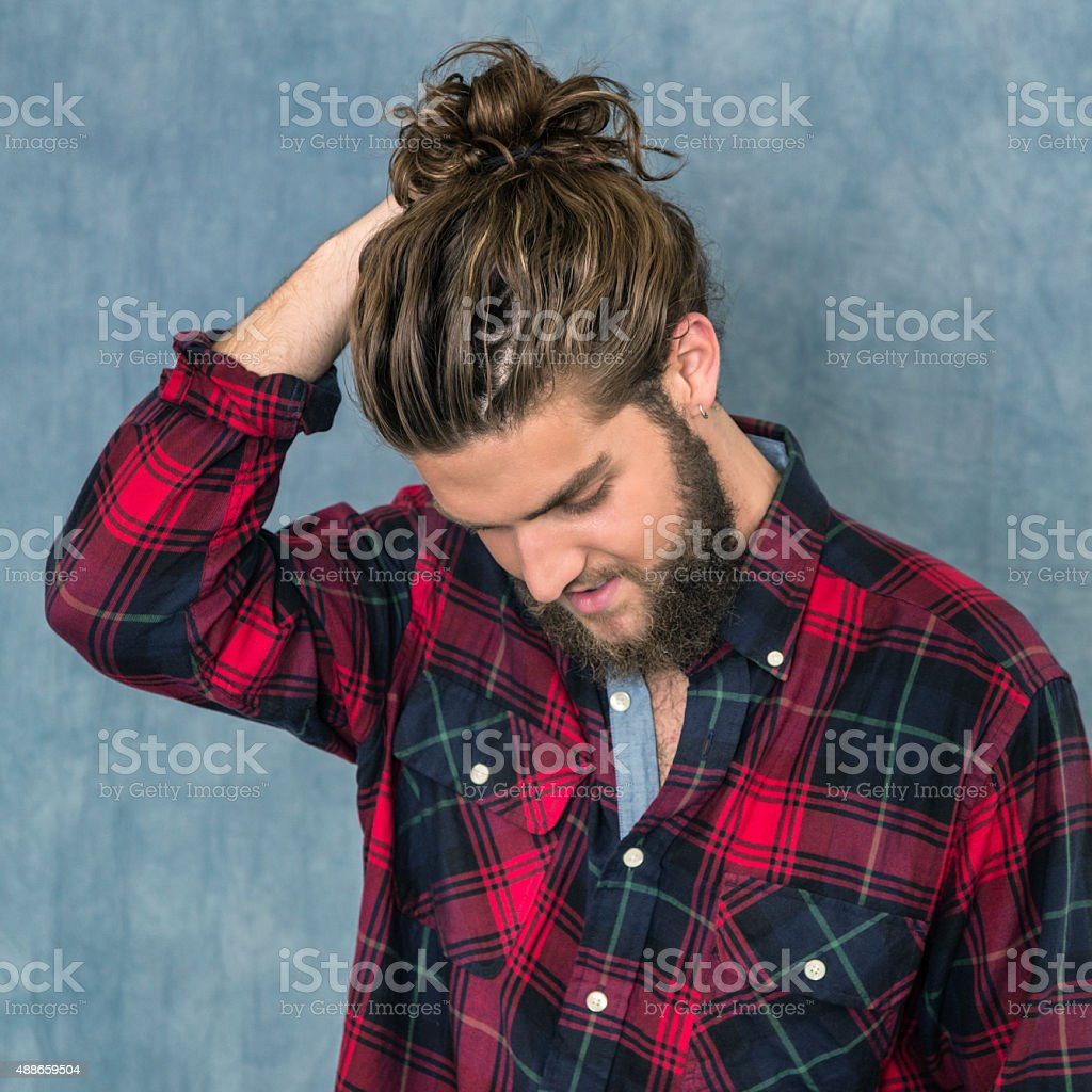 Young Man Adjusting Hair Bun stock photo