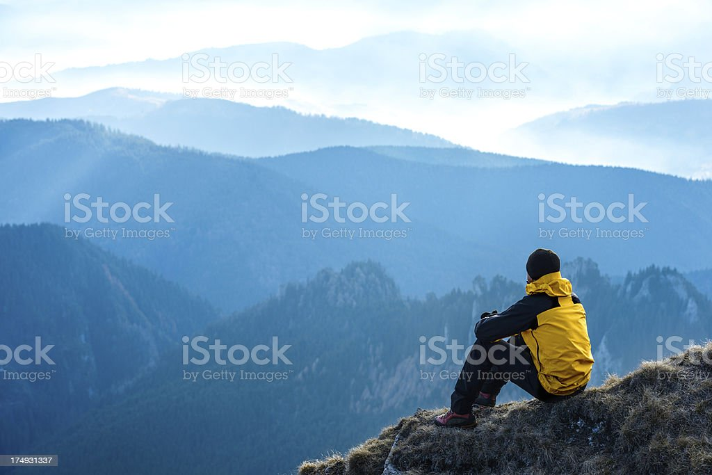 A young man admiring a distant mountain view royalty-free stock photo