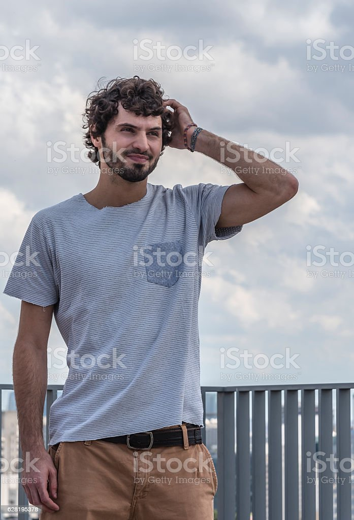 Young man alone and pensive in open place stock photo