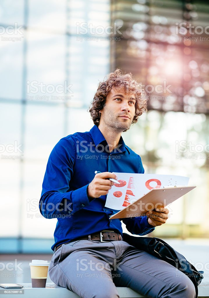Young man analyzing business data and finance charts stock photo
