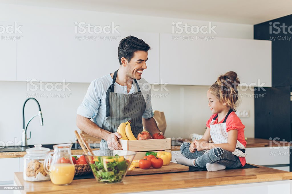 Young man and a small girl in the kitchen stock photo