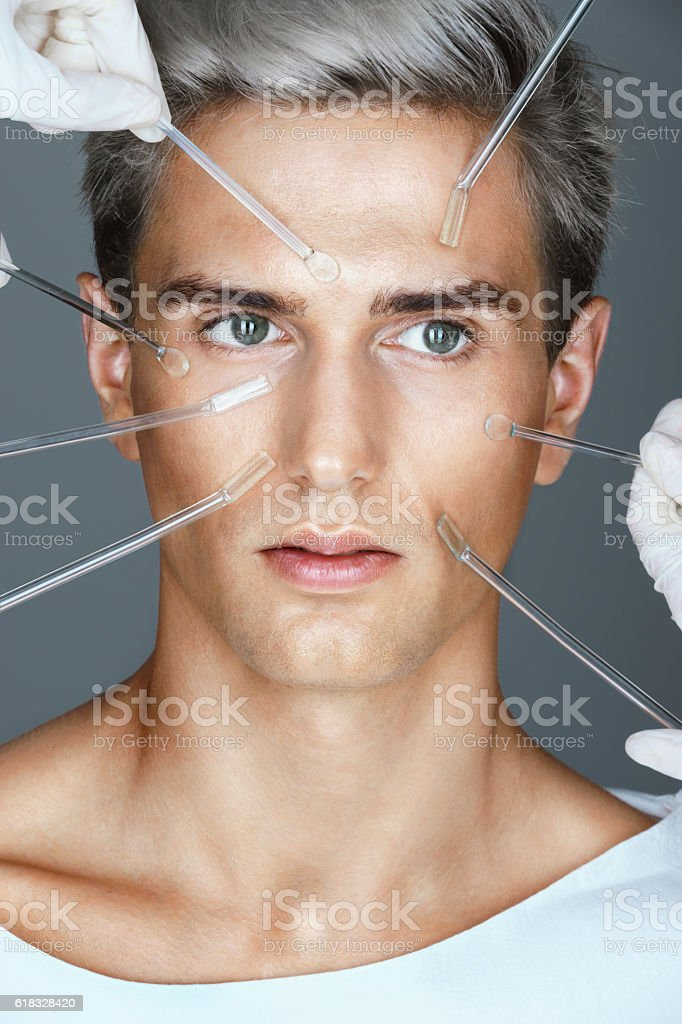 Young man and beautician hands with glass cream sticks. stock photo