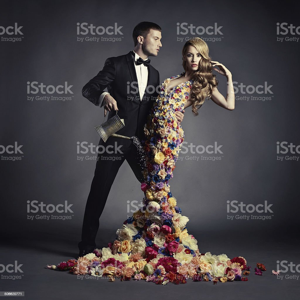 Young man and beautiful lady in flower dress stock photo