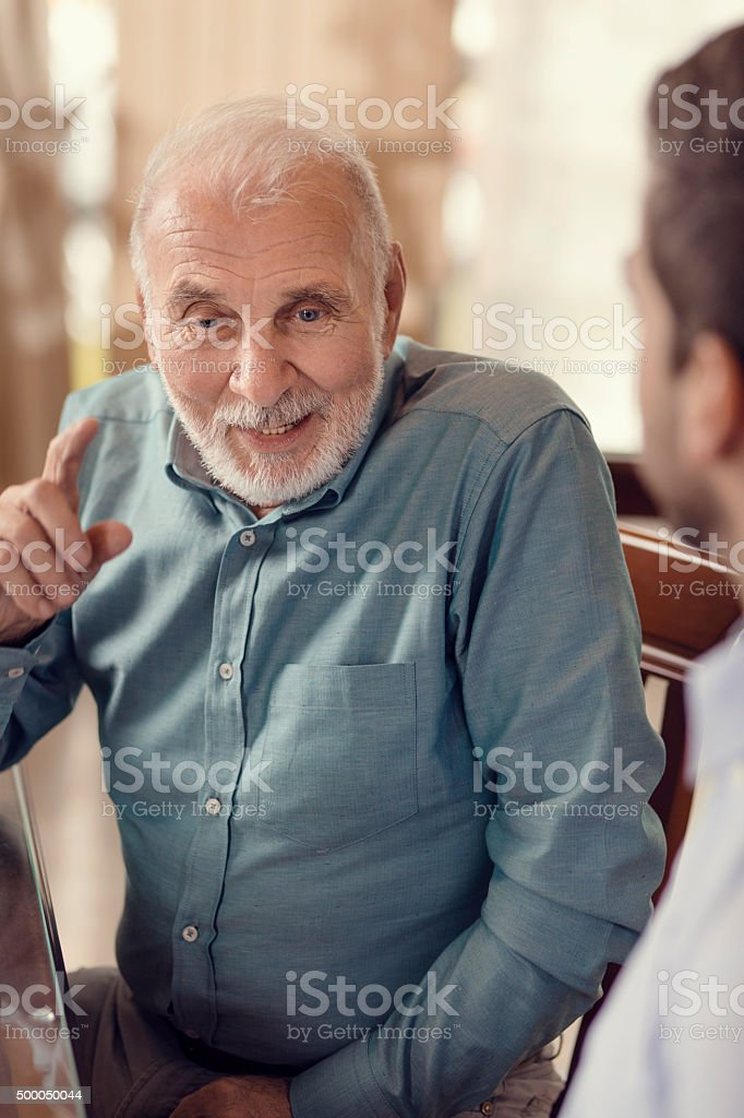 Young Man And His Grandfather In The Restaurant stock photo