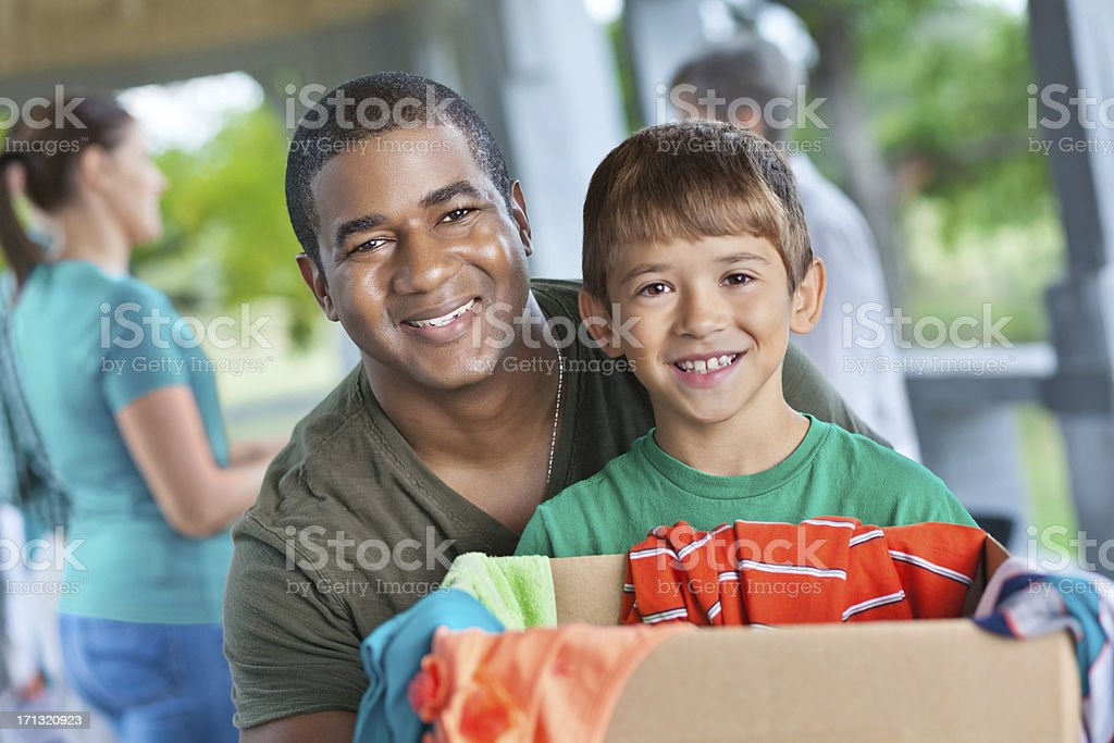 Young man and little boy collecting donations at charity event royalty-free stock photo