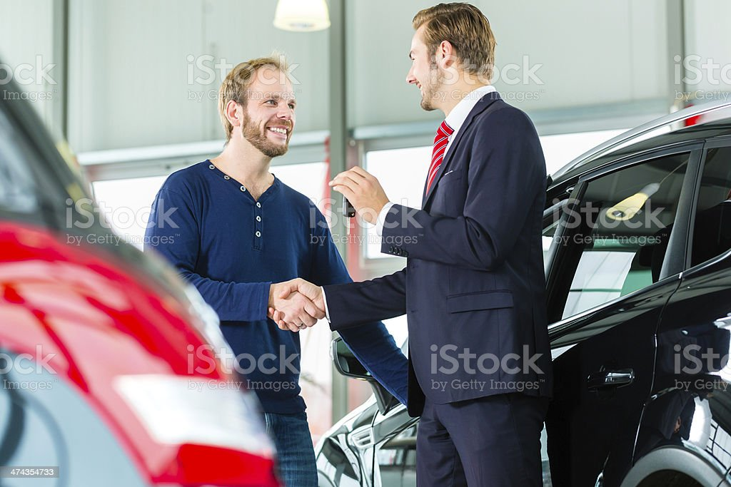 Young man and seller with auto in car dealership stock photo
