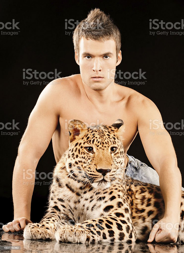 Young man and spotty leopard stock photo