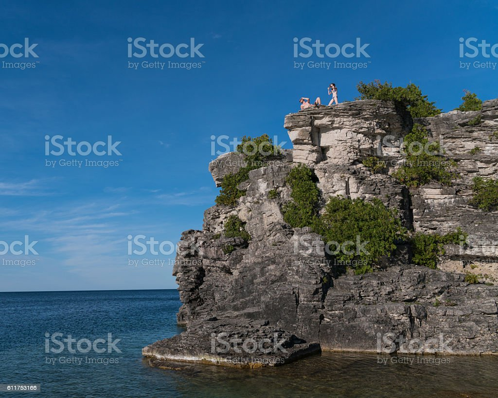 Young man and teenager girl on the cliff in Tobermory stock photo