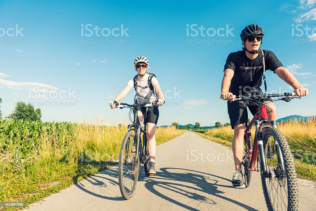 Young man and woman biking in nature stock photo