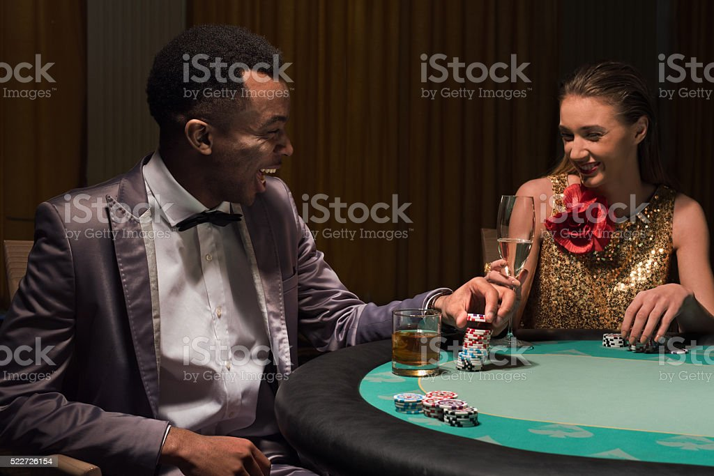 Young man and woman chatting at the poker table stock photo