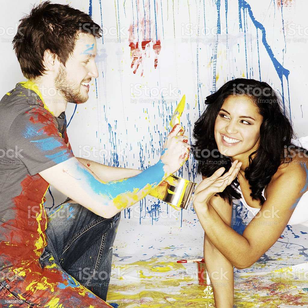 Young Man and Woman Covered in Different Colored Paint royalty-free stock photo