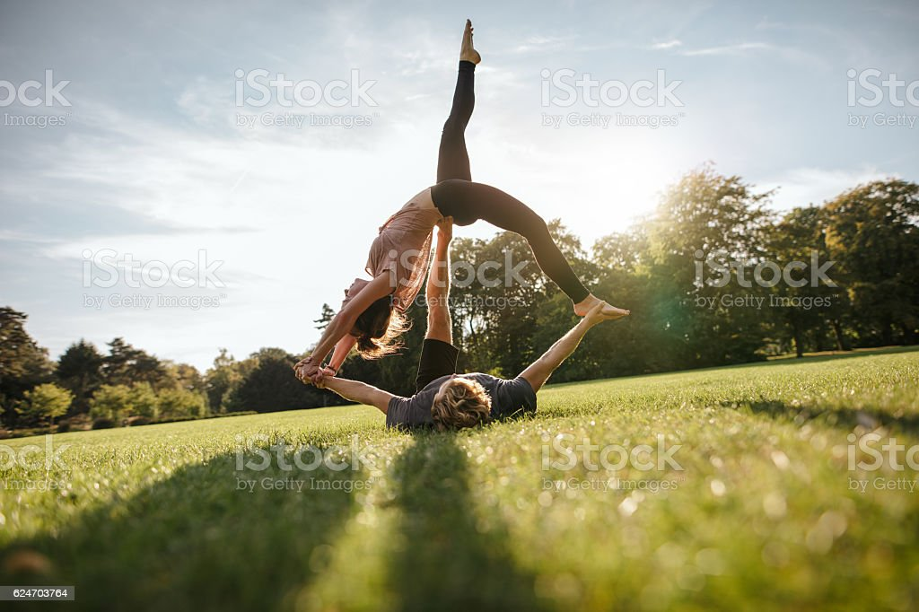 Young man and woman doing yoga in pair stock photo