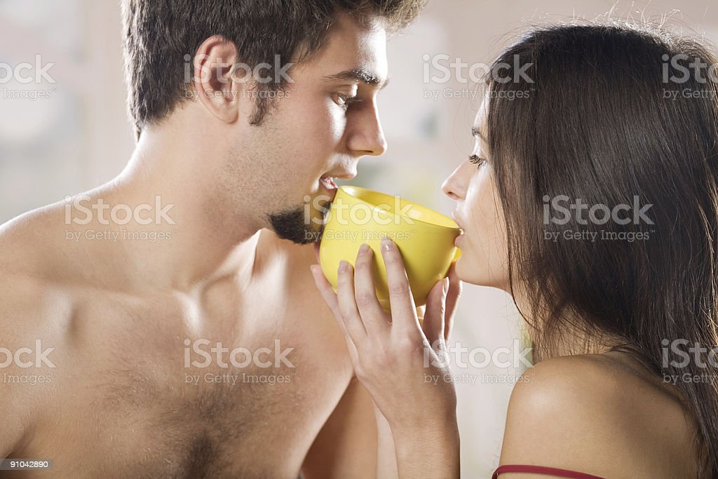 A young man and woman drinking from a yellow cup together royalty-free stock photo