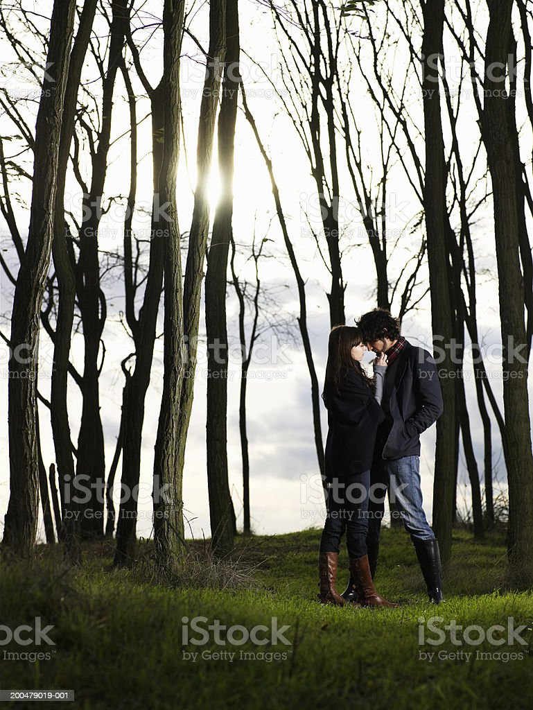 Young man and woman embracing beside grove of autumnal trees stock photo