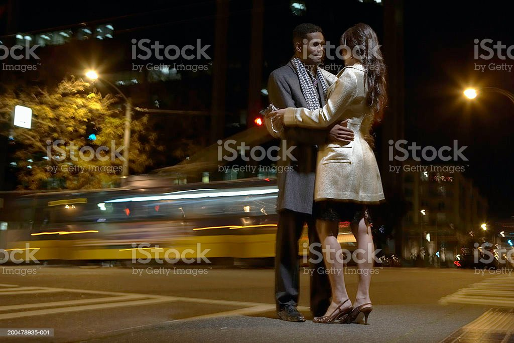 Young man and woman embracing outdoors at night (blurred motion) royalty-free stock photo