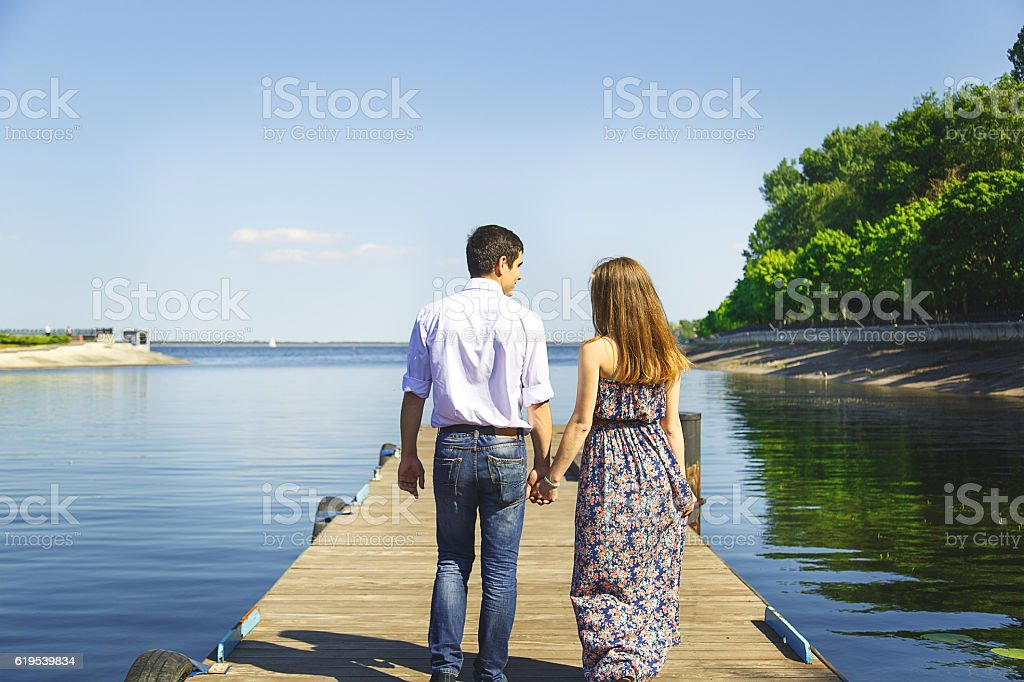 Young man and woman goes hand in hand on pier stock photo