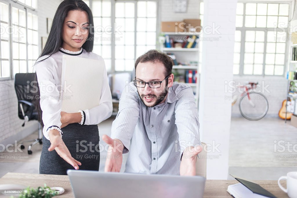 Young man and woman having problems at the office stock photo