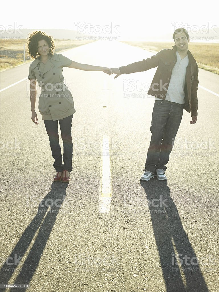 Young man and woman holding hands in middle of road at sunset royalty-free stock photo