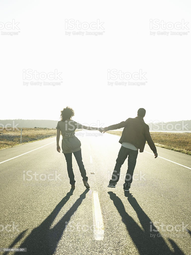 Young man and woman holding hands in middle of road, sunset, rear view royalty-free stock photo