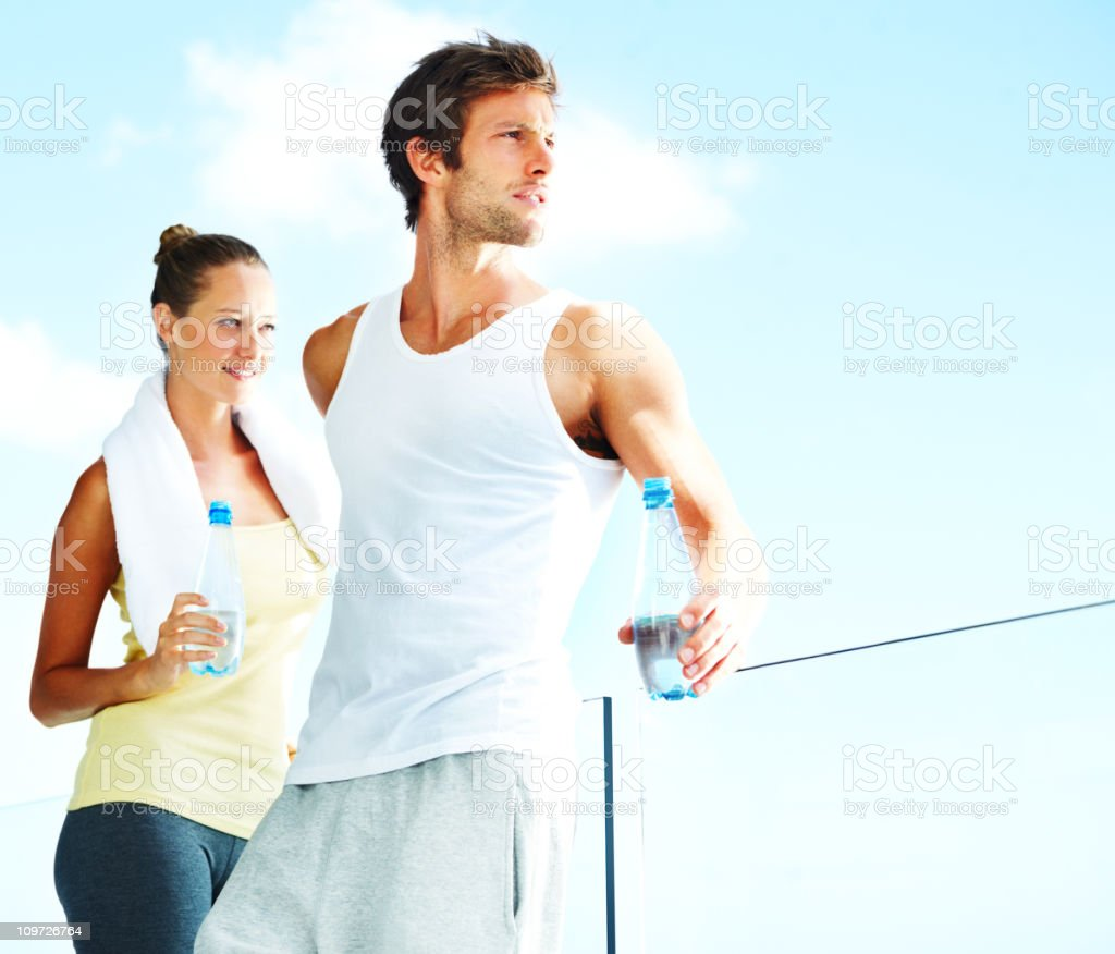 Young man and woman holding water bottles royalty-free stock photo