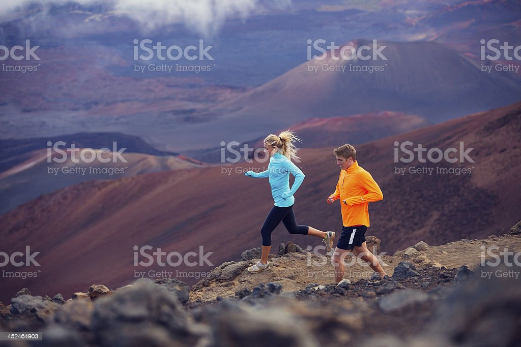 Young man and woman in fitness gear jogging stock photo