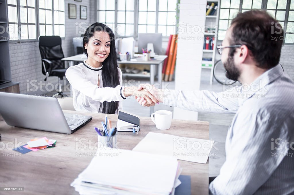 Young man and woman in handshake in the office stock photo