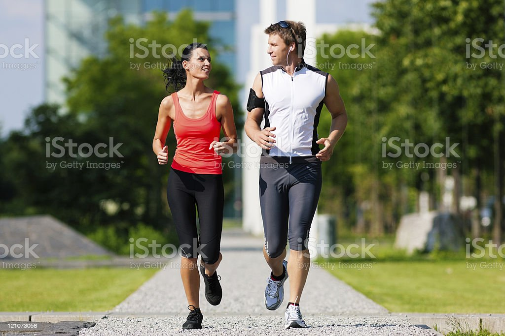 Young man and woman jogging in the city in summer royalty-free stock photo