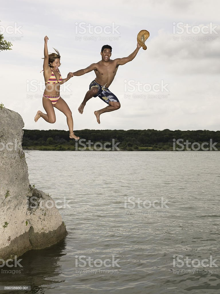 Young man and woman jumping off rock into lake, holding hands royalty-free stock photo