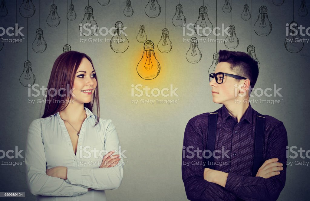 Young man and woman looking at bright light bulb each other stock photo