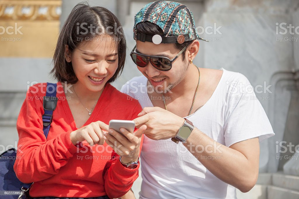 young man and woman looking to smart phone stock photo