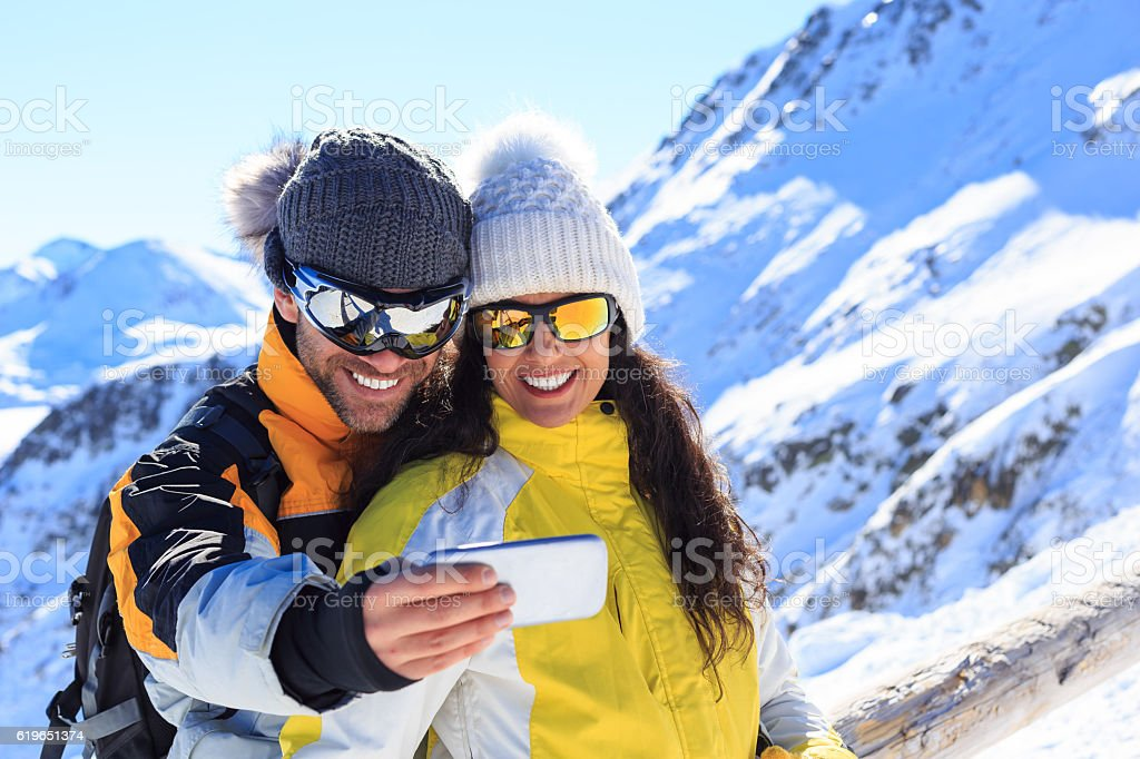 Young man and woman making selfie on snow mountain stock photo