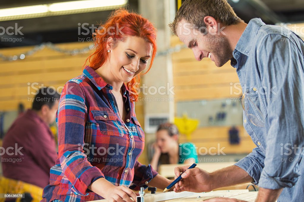 Young man and woman measuring boards in makerspace workshop stock photo