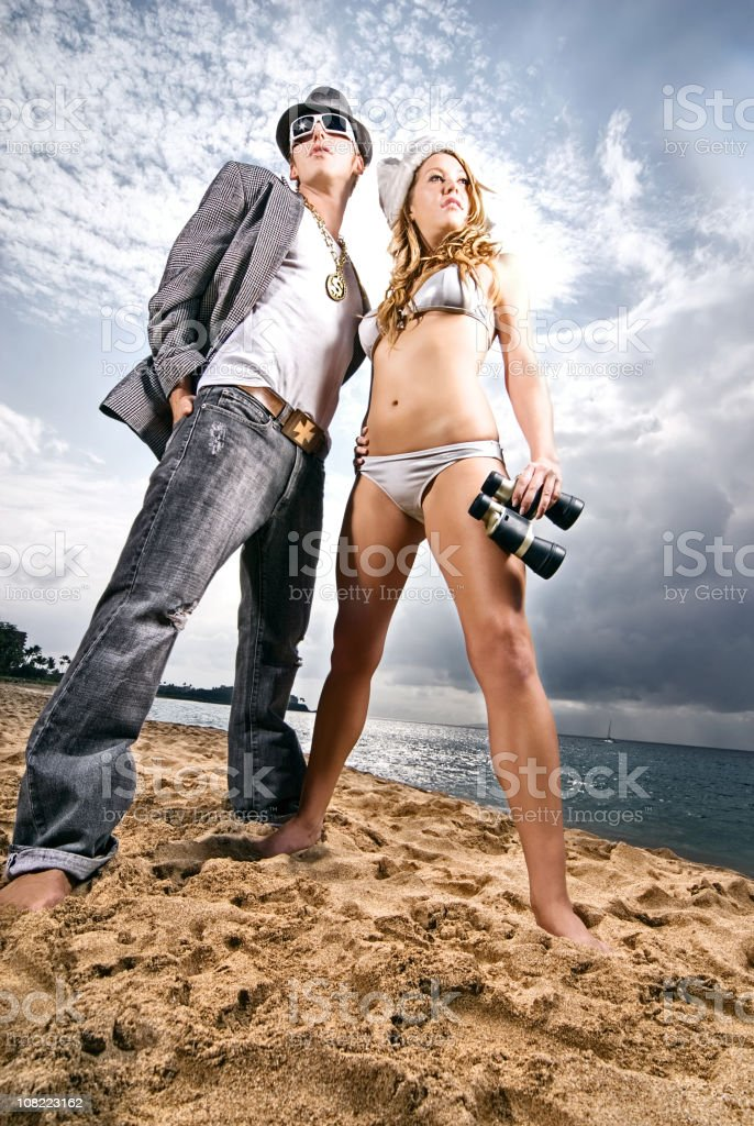 Young Man and Woman on Beach with Binoculars stock photo